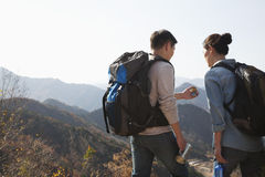 Young couple hiking and looking at the compass Royalty Free Stock Photo