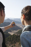 Young couple hiking and looking at the compass Stock Image