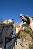 Young couple hiking, man helping woman up bank, low angle view Stock Photo