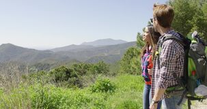 Young couple hiking in mountains. Two young people hiking in summer time and pointing away while laughing on background of mountains stock footage
