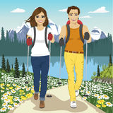 Young couple hiking outdoors with backpacks in summer mountains Royalty Free Stock Image
