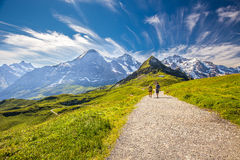 Young couple hiking in panorama trail leading to Kleine Scheidegg from Mannlichen with Eiger, Monch and Jungfrau mountain. (Swiss Alps) in the background royalty free stock image