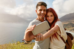 Young couple hiking taking selfie with smart phone Royalty Free Stock Image