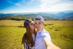 Young couple hiking taking selfie with smart phone. Happy young man and woman taking self portrait with mountain scenery stock photo