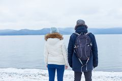 young couple is hiking on a winter lake royalty free stock photos