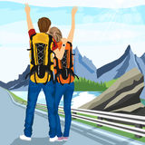 Young couple of hitchhikers standing on road and enjoying mountain scenery Stock Images