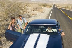 Young couple hitchhiking on desert road, in conversation with driver of car, elevated view Stock Photography