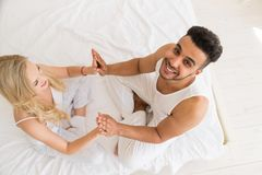 Young Couple Hold Hands Sitting In Bed, Happy Smile  Hispanic Man And Woman Top Angle View Royalty Free Stock Images