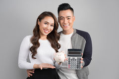 Young couple hold pink pig bank and calculator standing over on Royalty Free Stock Photography