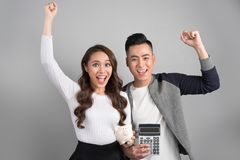 Young couple hold pink pig bank and calculator standing over on Royalty Free Stock Images