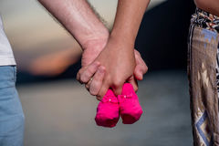 Young couple holding baby shoes.  Stock Image