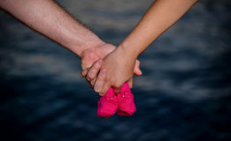 Young couple holding baby shoes. In their hands Royalty Free Stock Photography