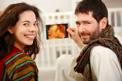 Young couple holding baby ultrasound image. Happy young couple holding baby ultrasound image in nursery. Looking back at camera, smiling Stock Photography