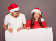 Young couple holding billboard in Christmas Royalty Free Stock Image