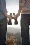 Young couple holding binoculars and looking at the sun Stock Images