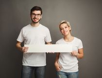 Young couple holding blank white banner Royalty Free Stock Image