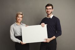 Young couple holding blank white banner. Happy young couple holding blank white banner with copy space on gray background Royalty Free Stock Photo