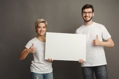 Young couple holding blank white banner. Happy young couple holding blank white banner with copy space and showing thumb up on gray background Royalty Free Stock Photography