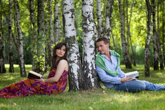 Young couple holding books in park Stock Image