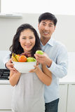 Young couple holding bowl full of fruit in kitchen Royalty Free Stock Images