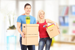 Young couple holding boxes and posing at new home Stock Image