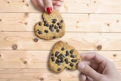 Young couple holding chocolate cookies in shape of hearts against wooden table, as love symbol. Young couple holding chocolate cookies in shape of hearts against stock photography