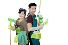 Young couple holding cleaning supplies on studio Royalty Free Stock Images