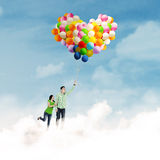 Young couple holding colorful balloons Royalty Free Stock Image