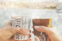 A young couple  is holding cups of coffee in front of sea and blurred view ,love story ,close up. A young couple a man and woman ,holding cups of coffee in front Stock Images