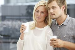 Young couple holding cups Stock Image