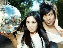 Young couple holding disco mirror ball. Attractive young couple holding disco mirror ball. Image cross processed Stock Images