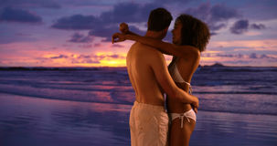 Young couple holding each other on beach watching ocean waves. Young couple holding each other on beach watching ocean waves Stock Images