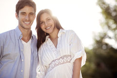 Young couple holding eachother in a park. Young couple hugging outdoors in the sun Royalty Free Stock Photo