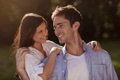 Young couple holding eachother in a park. Young couple hugging outdoors in the sun Royalty Free Stock Images