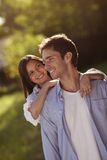 Young couple holding eachother in a park. Young couple hugging outdoors in the sun Stock Image