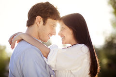 Young couple holding eachother in a park. Young couple hugging outdoors in the sun Stock Photography