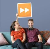 Young couple holding a fast forward button icon royalty free stock photo