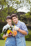Young couple holding freshly harvested vegetables Stock Image