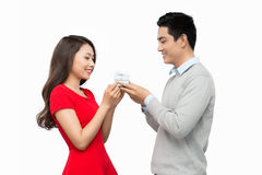 Young couple holding a gift box over whiite background Royalty Free Stock Photo
