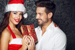 Young couple holding gift at Christmas, santa woman with boyfrie Royalty Free Stock Photo
