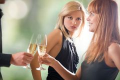 Young couple holding glasses with champagne and woman looking Stock Images