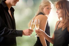 Young couple holding glasses with champagne and woman looking Stock Photography