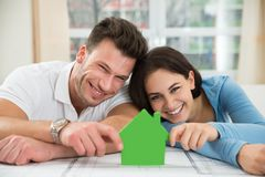 Young couple holding green house model Royalty Free Stock Image