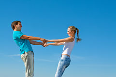 Young couple holding hands. Against blue sky Royalty Free Stock Image