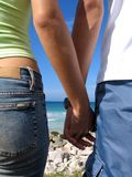 Young couple holding hands. Detail of young couple holding hands on beach background Stock Photo