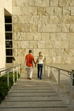 Young couple holding hands. Going down a set of stairs royalty free stock photo