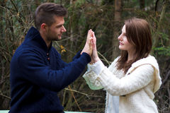 Young couple holding hands. In the forest in front of trees Royalty Free Stock Photos