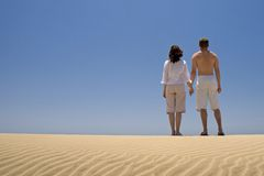 Young couple holding hands. On the sand dunes in Gran Canaria royalty free stock images