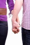 Young couple holding hands. Bodies and arms of young couple in love holding hands, isolated on white background Royalty Free Stock Images
