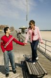 Young couple holding hands. Young couple walking along the seafront on a date Stock Photos